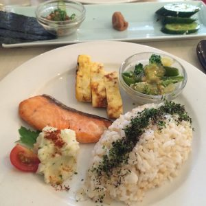 Japanese breakfast (clockwise from top left): nori, natto, salted plum, pickles, broccoli and snap peas with tofu in miso dressing, rice, potato salad, grilled salmon, omelette